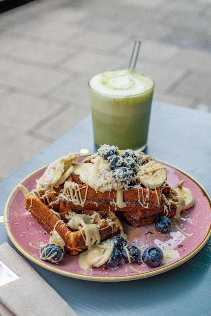 Vegane Waffel mit Obst und Mandelmus auf einem pinken Teller im Café Om Nom Nom in Sendling