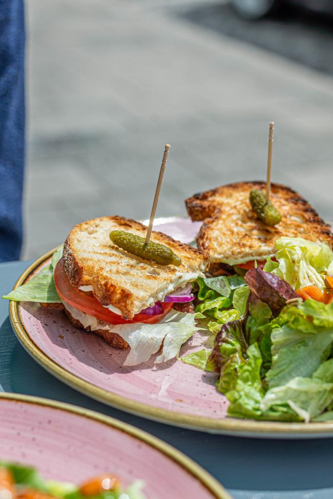 Ein Teller mit zwei Sandwichhälften und Salat aus dem veganen Café Om Nom Nom in Sendling